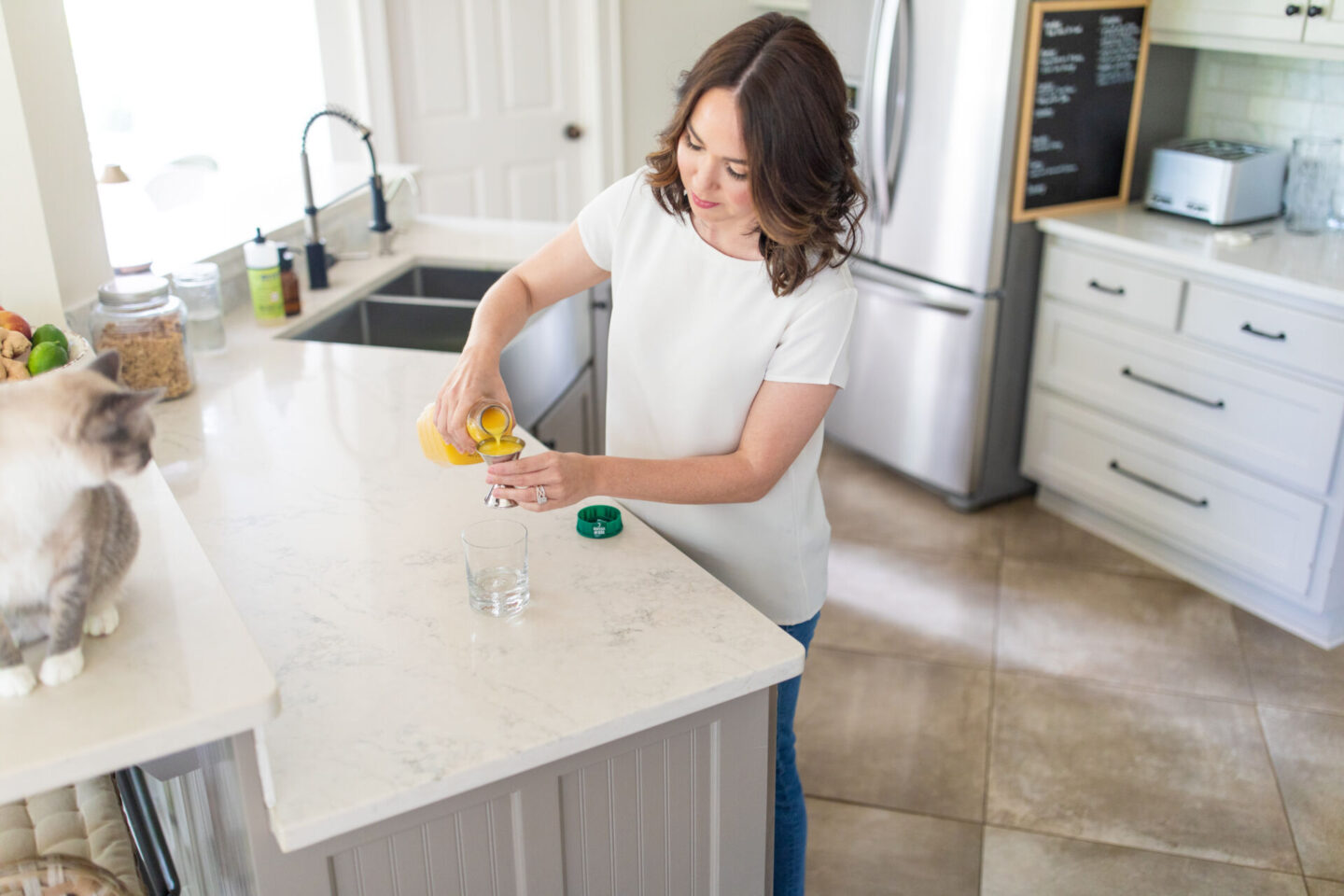 Coconut Rum Punch Recipe featured by top Atlanta lifestyle blogger, Moderately High Maintenance | Coconut Rum Punch by popular Atlanta lifestyle blog, Moderately High Maintenance: image of a woman pouring some orange juice into a jigger.