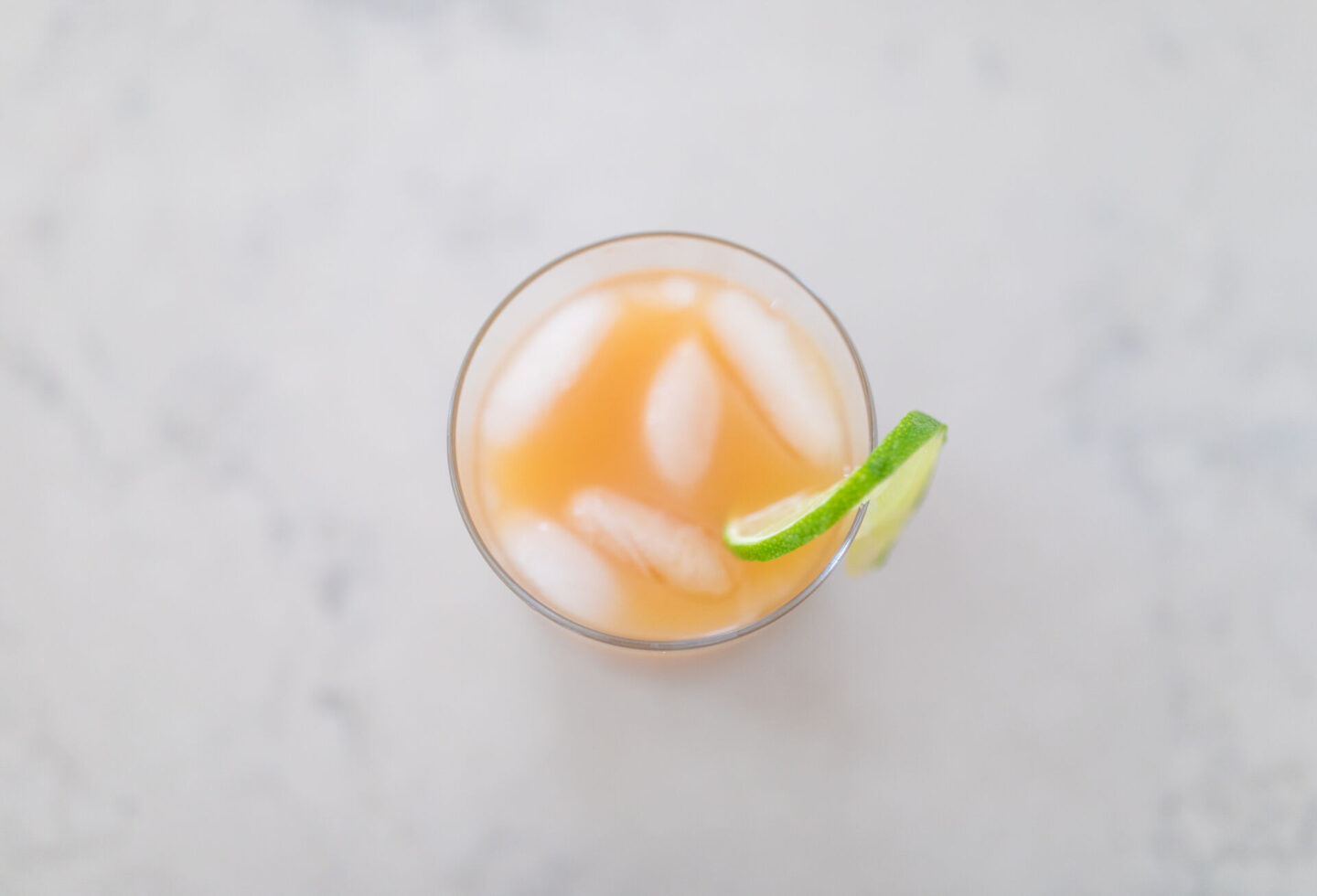 Coconut Rum Punch Recipe featured by top Atlanta lifestyle blogger, Moderately High Maintenance | Coconut Rum Punch by popular Atlanta lifestyle blog, Moderately High Maintenance: image of coconut rum punch in a clear glass with a lime wedge garnish.