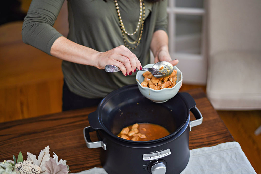 Calphalon Crock Pot Recipe: Ginger Teriyaki Chicken featured by top Atlanta lifestyle blogger, Moderately High Maintenance |Ginger Teriyaki Chicken by popular Atlanta lifestyle blog, Moderately High Maintenance: image of a woman scooping ginger teriyaki chicken out of a Calphalon pressure cooker.