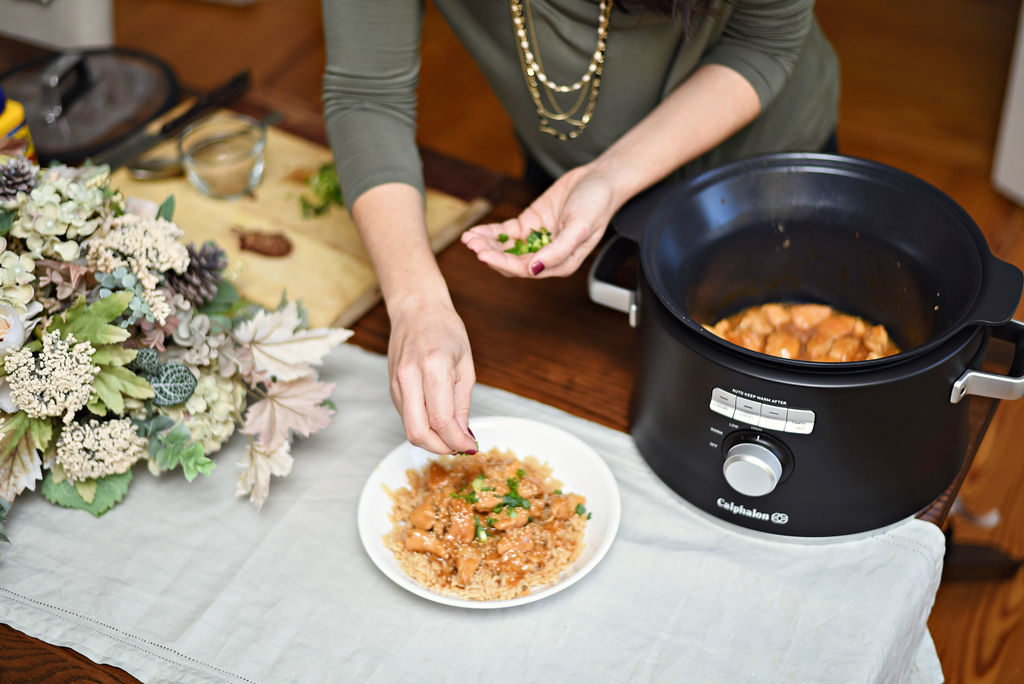 Calphalon Crock Pot Recipe: Ginger Teriyaki Chicken featured by top Atlanta lifestyle blogger, Moderately High Maintenance |Ginger Teriyaki Chicken by popular Atlanta lifestyle blog, Moderately High Maintenance: image of a woman putting chopped green onions on a plate of ginger teriyaki chicken.