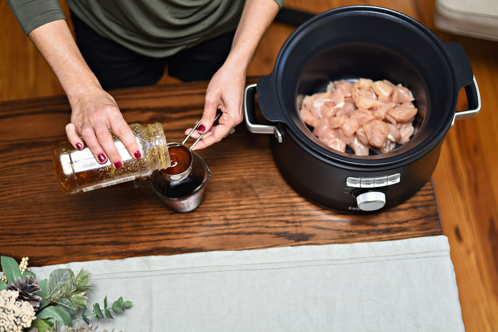 Calphalon Crock Pot Recipe: Ginger Teriyaki Chicken featured by top Atlanta lifestyle blogger, Moderately High Maintenance |Ginger Teriyaki Chicken by popular Atlanta lifestyle blog, Moderately High Maintenance: image of a woman standing next to a Calphalon pressure cooker filled with raw chicken pieces and filling a measuring cup with teriyaki sauce.