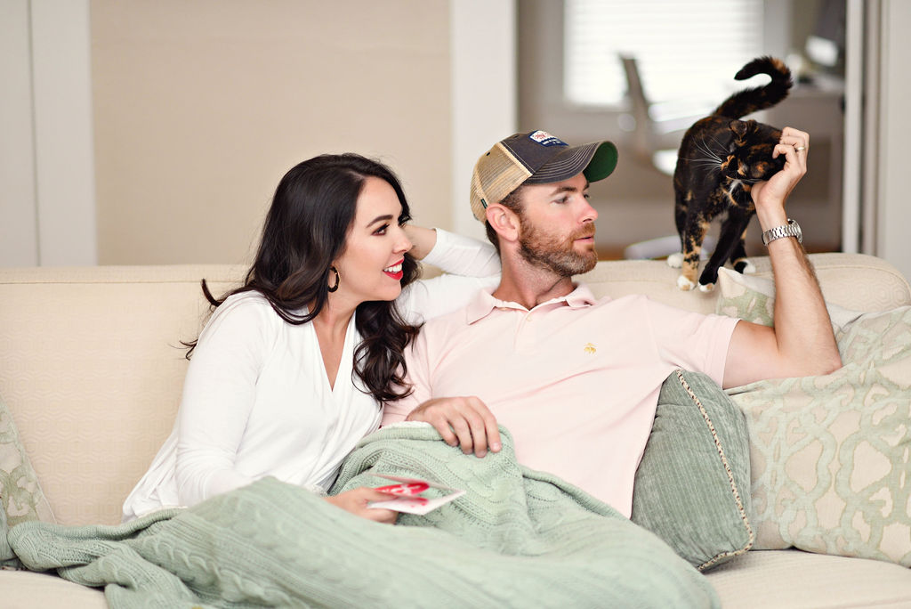 Amazon Valentine's Day Cards by popular Atlanta lifestyle blog, Moderately High Maintenance: image of a woman holding a Amazon Valentine's Day card and while sitting on under a green knit blanket on a couch next to her husband and their cat.