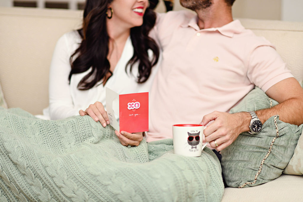 Amazon Valentine's Day Cards by popular Atlanta lifestyle blog, Moderately High Maintenance: image of a woman holding a Amazon Valentine's Day card and while sitting on under a green knit blanket on a couch next to her husband.