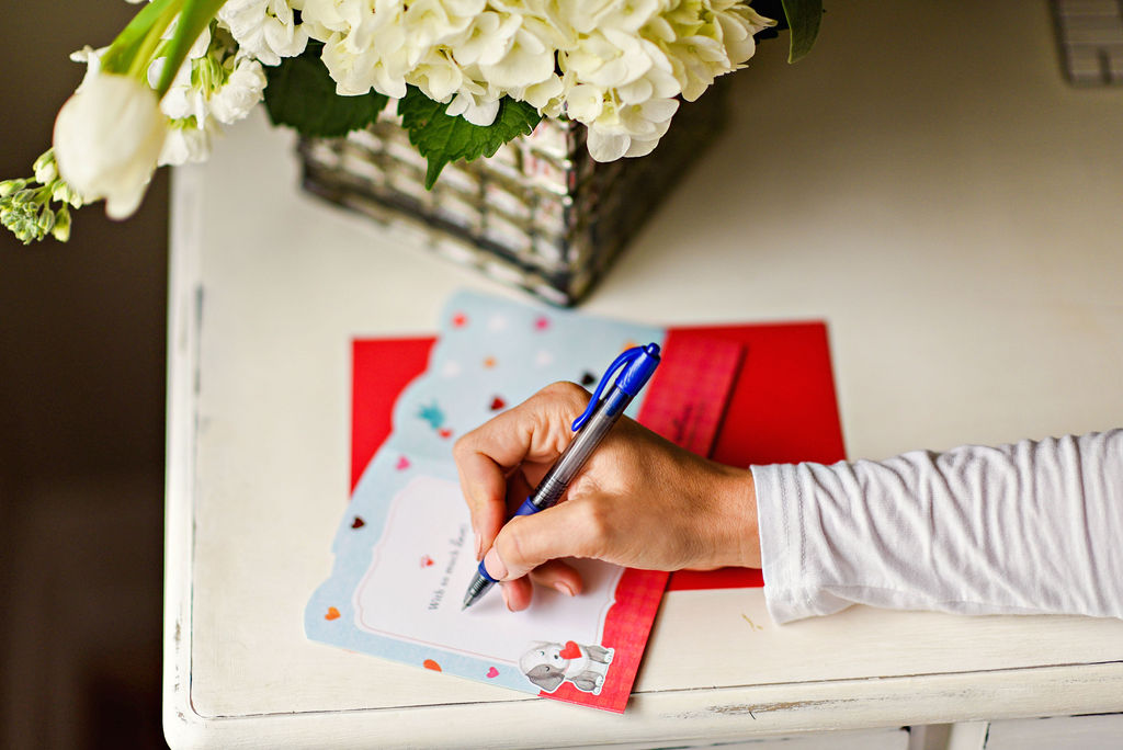 Amazon Valentine's Day Cards by popular Atlanta lifestyle blog, Moderately High Maintenance: image of a woman writing inside a Amazon Valentine's Day card.