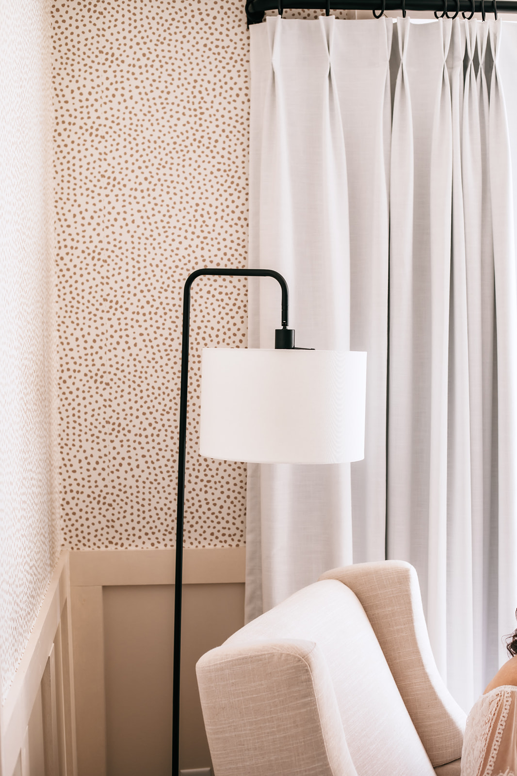 Gender Neutral Nursery by popular Atlanta lifestyle blog, Moderately High Maintenance: image of a nursery with taupe dot wallpaper, board and batten wall, black stand modern floor lamp, white curtains, and beige rocker.