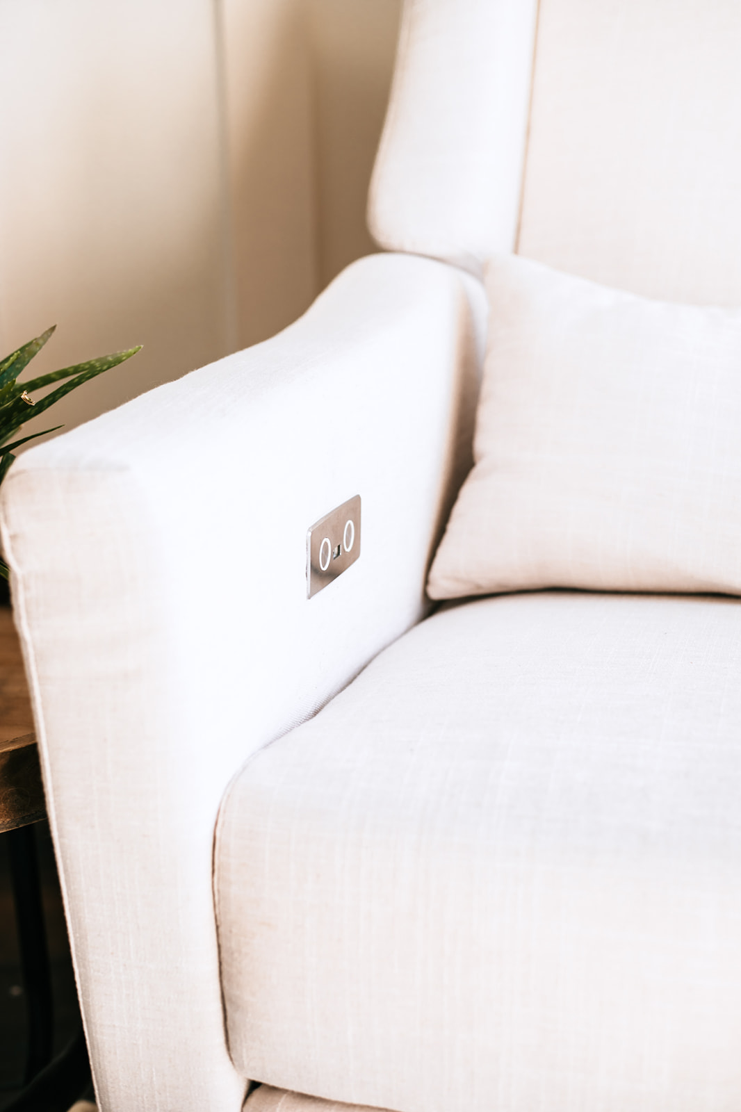 Gender Neutral Nursery Glider |Gender Neutral Nursery by popular Atlanta lifestyle blog, Moderately High Maintenance: image of a cream glider with a charging port. .