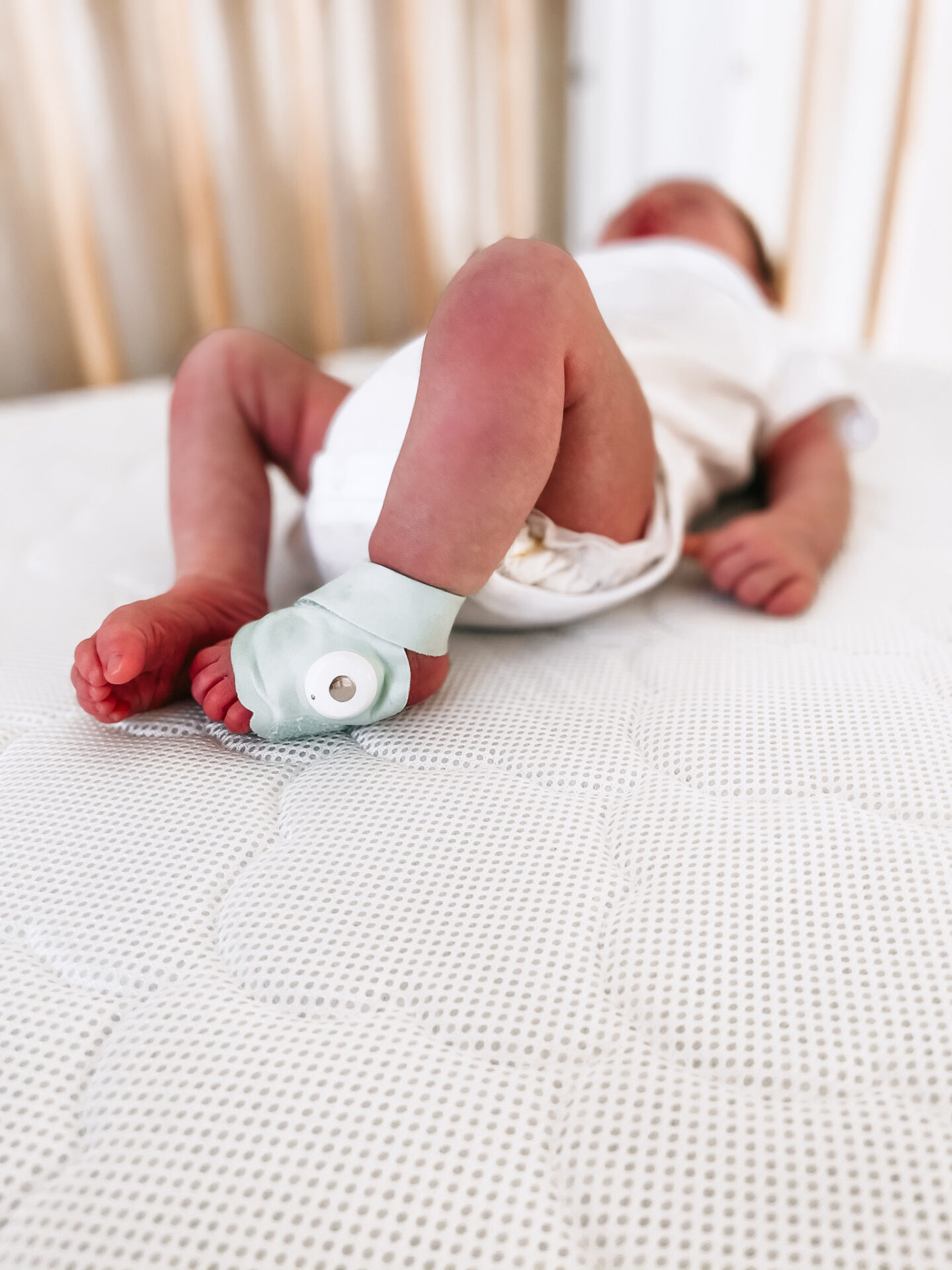 Best Baby Items by popular Atlanta motherhood blog, Moderately High Maintenance: image of a baby wearing a Owlet Baby monitor foot attachment.