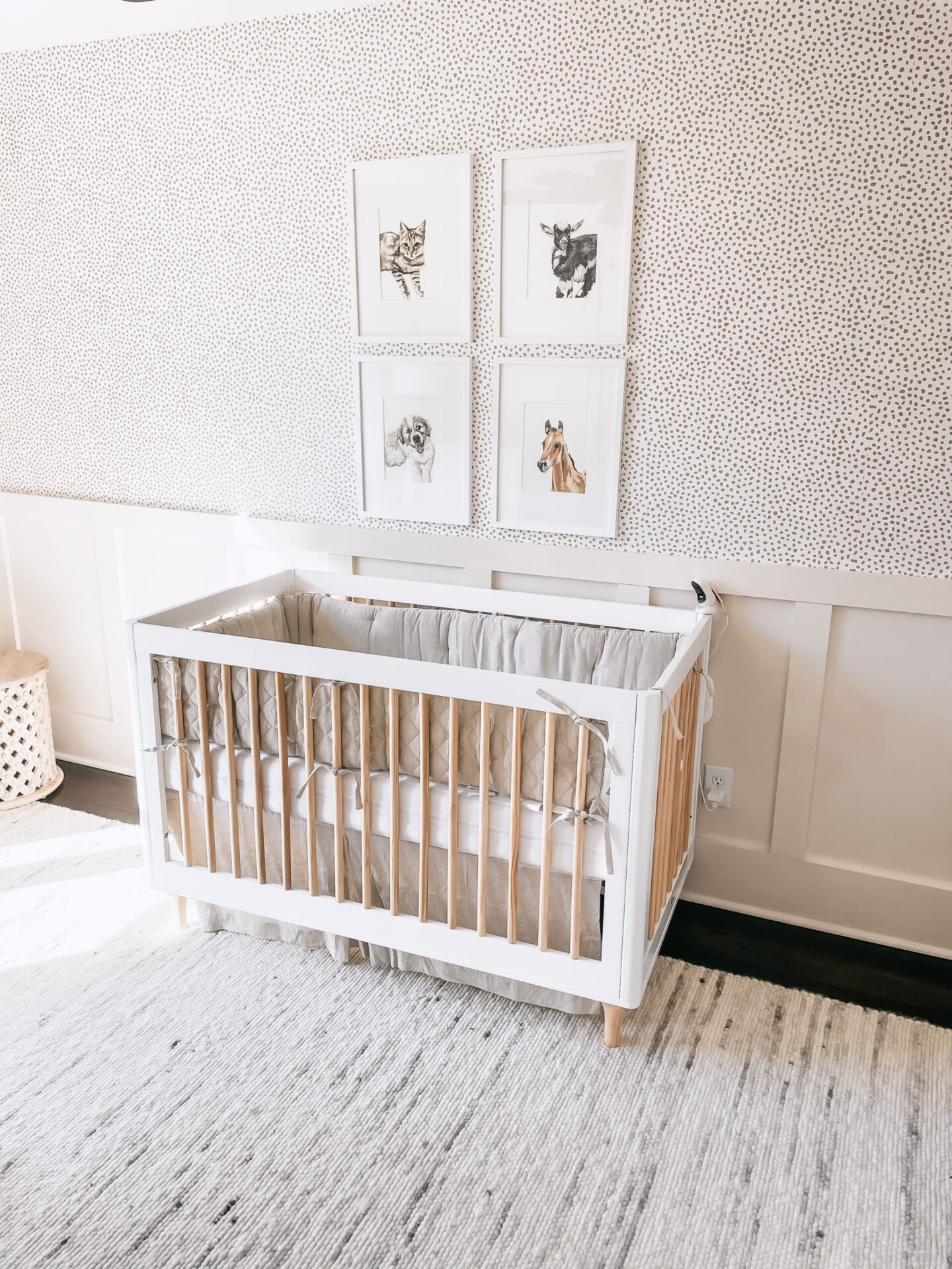 Gender Neutral Nursery by popular Atlanta lifestyle blog, Moderately High Maintenance: image of a nursery with taupe dot wallpaper, board and batten wall, black stand modern floor lamp, white curtains, white rug,white framed animal prints, white and wood crib with grey crib bedding, round wooden table, and beige rocker.