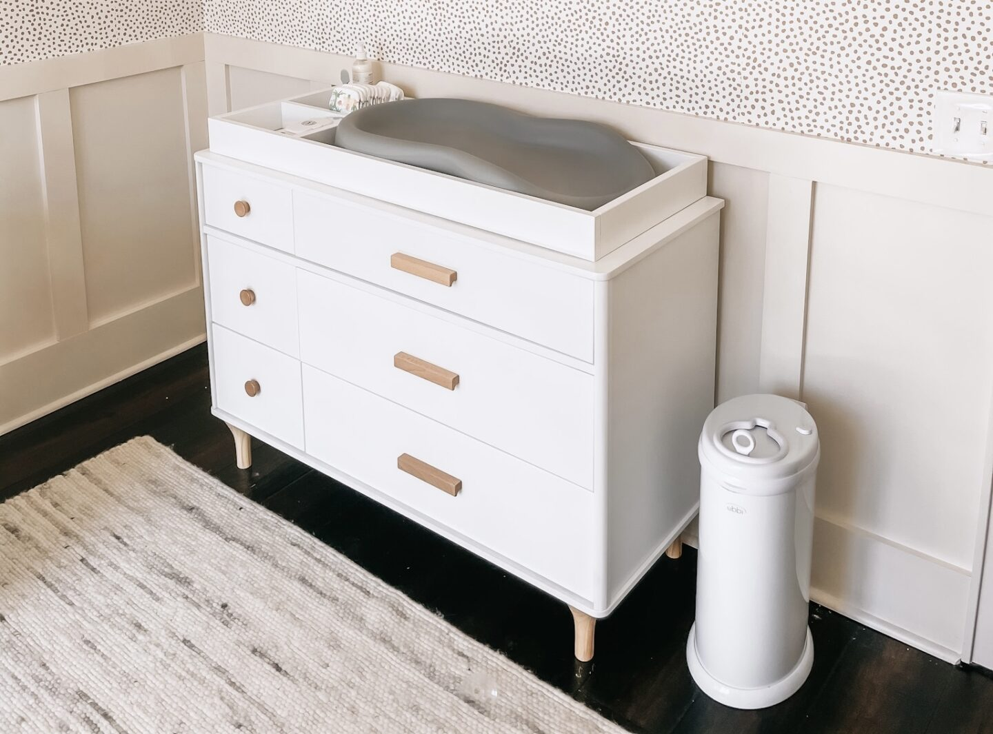 Gender Neutral Nursery by popular Atlanta lifestyle blog, Moderately High Maintenance: image of a nursery with taupe dot wallpaper, board and batten wall, white changing table, white diaper pail, and white and grey rug.