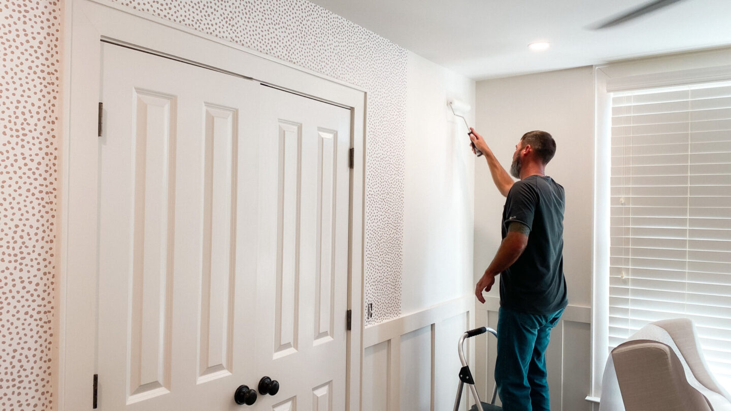 Gender Neutral Nursery by popular Atlanta lifestyle blog, Moderately High Maintenance: image of a person applying taupe dot wallpaper to a wall.