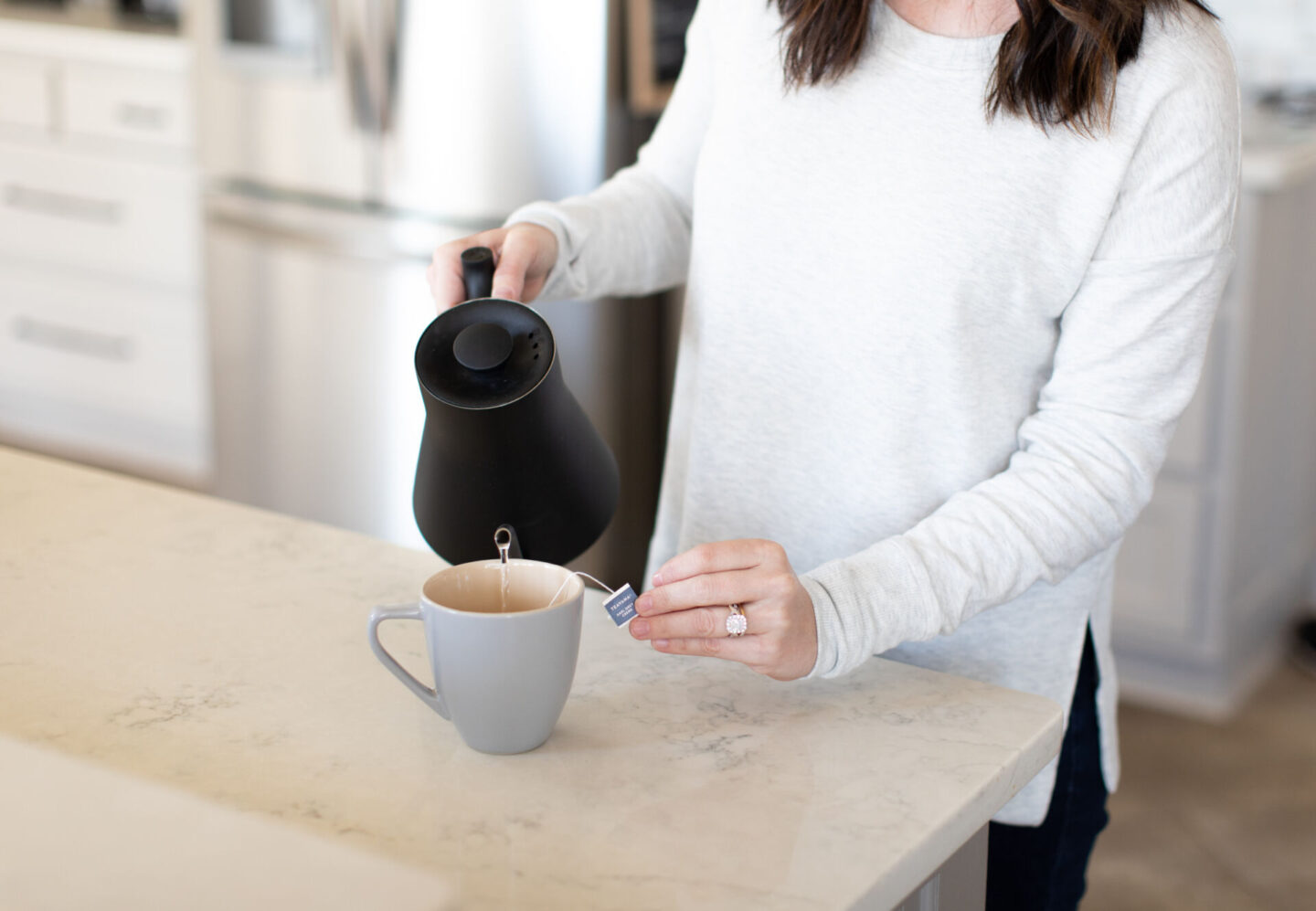 Vegan London Fog by popular Atlanta lifestyle blog, Moderately High Maintenance: image of a woman pouring water from a black kettle in to a grey ceramic mug.