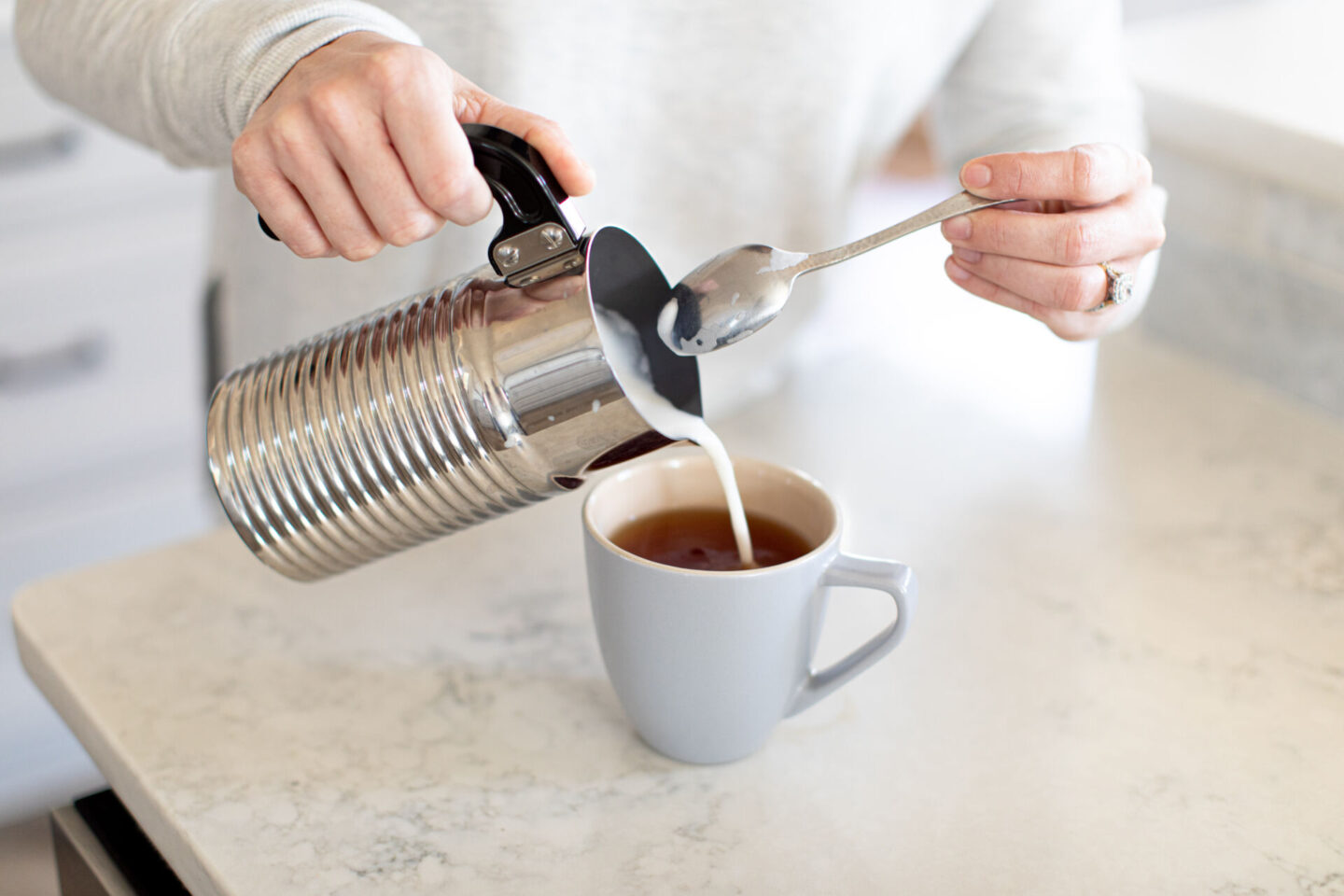 Vegan London Fog by popular Atlanta lifestyle blog, Moderately High Maintenance: image of a woman milk from a frother into grey ceramic mug.