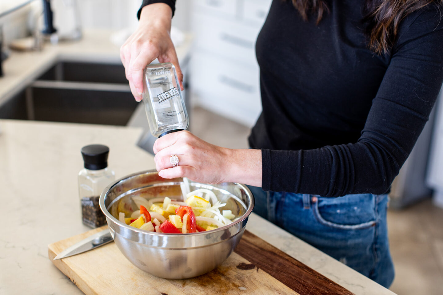EASY Sheet Pan Roasted Vegetables Recipe featured by top Atlanta lifestyle blogger, Moderately High Maintenance |Pan Roasted Vegetables by popular Atlanta lifestyle blog, Moderately High Maintenance: image of a woman seasoning chopped vegetables in a metal bowl.