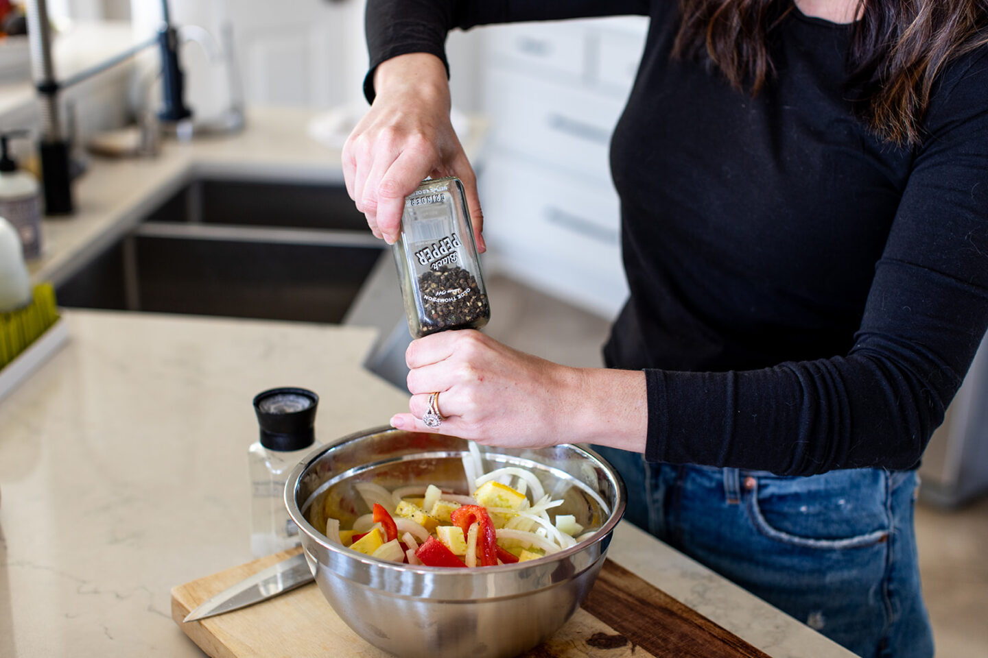EASY Sheet Pan Roasted Vegetables Recipe featured by top Atlanta lifestyle blogger, Moderately High Maintenance |Pan Roasted Vegetables by popular Atlanta lifestyle blog, Moderately High Maintenance: image of a woman seasoning some chopped vegetables in a metal mixing bowl.
