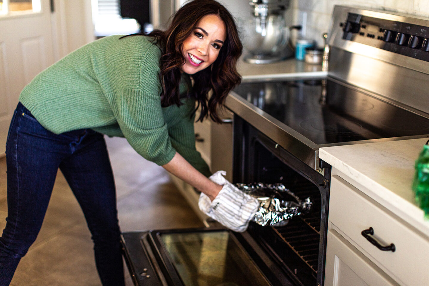 hibachi mushrooms recipe featured by top Atlanta lifestyle blogger, Moderately High Maintenance |Hibachi Mushrooms by popular Atlanta lifestyle blog, Moderately High Maintenance: image of a woman placing sliced mushrooms and chopped onions wrapped in tin foil in the oven.