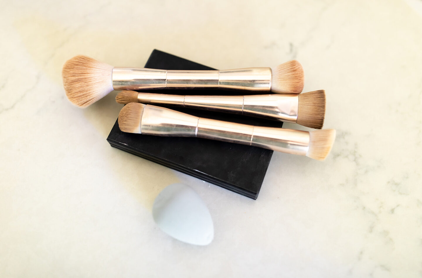 Seint Makeup: How to Contour Step by Step, a tutorial featured by top Seint artist, Madeleine of Moderately High Maintenance   Seint Makeup by popular Atlanta beauty blog, Moderately High Maintenance: image of gold handle makeup brush resting on a black compact next to a white beauty blender.