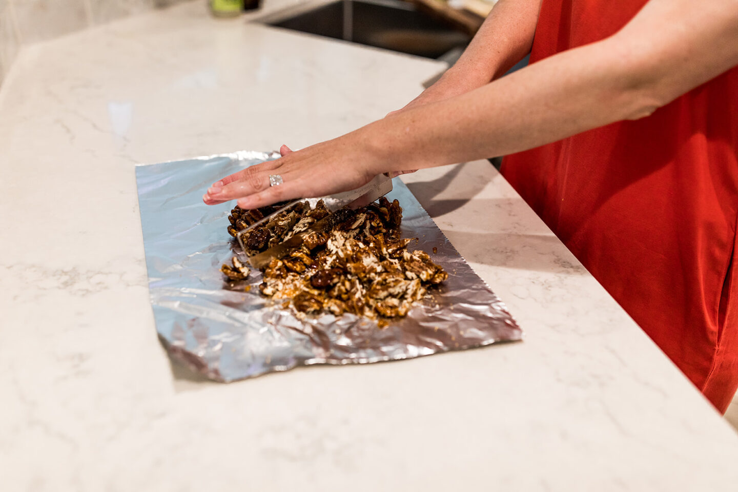 Simple Candied Pecans Recipe featured by top Atlanta lifestyle blogger, Moderately High Maintenance   Candied Pecans Recipe by pouplar Atlanta lifestyle blog, Moderately High Maintenance: image of a woman chopping some candied pecans on a sheet of tinfoil.