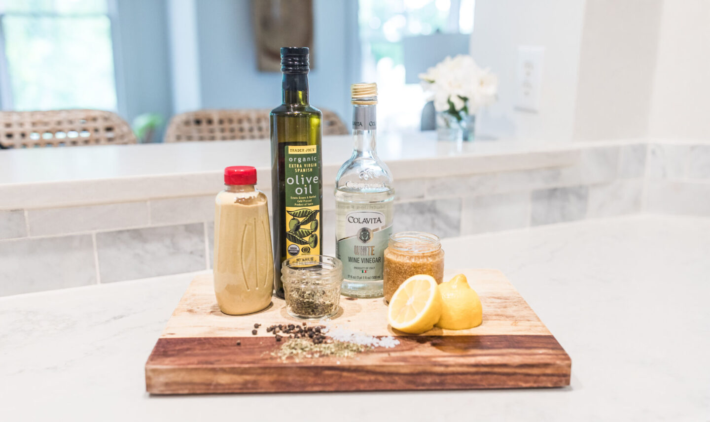 Easy Homemade Salad Dressing Recipe featured by top Atlanta lifestyle blogger, Moderately High Maintenance | Homemade Salad Dressing by popular Atlanta lifestyle blog, Moderately High Maintenance: image of olive oil, vinegar, lemons, minced garlic and spices on a wooden board.