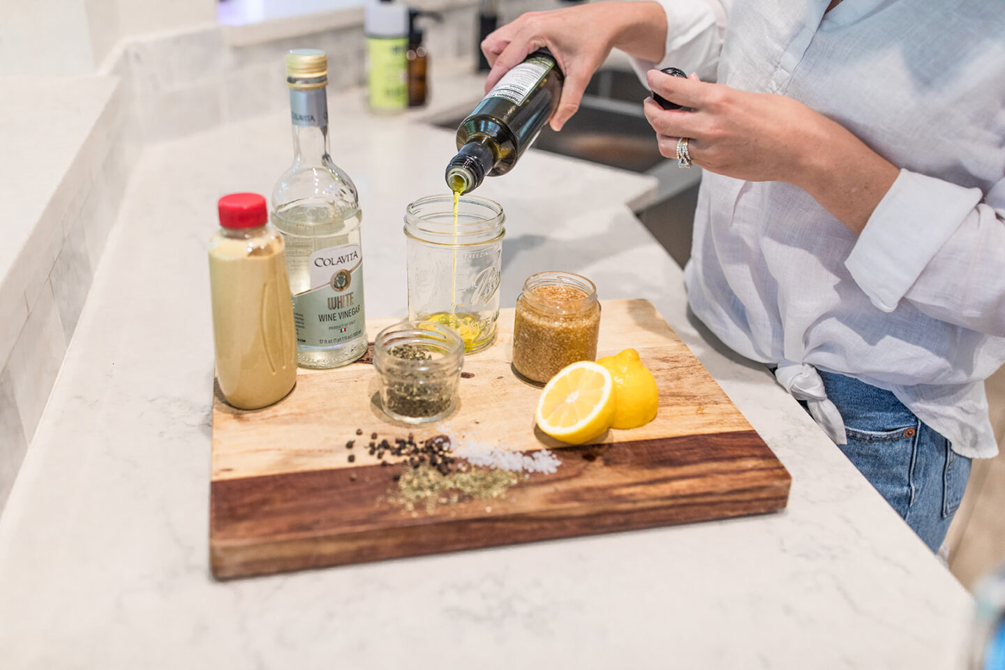 Easy Homemade Salad Dressing Recipe featured by top Atlanta lifestyle blogger, Moderately High Maintenance | Homemade Salad Dressing by popular Atlanta lifestyle blog, Moderately High Maintenance: image of a woman pouring olive oil into a mason jar.