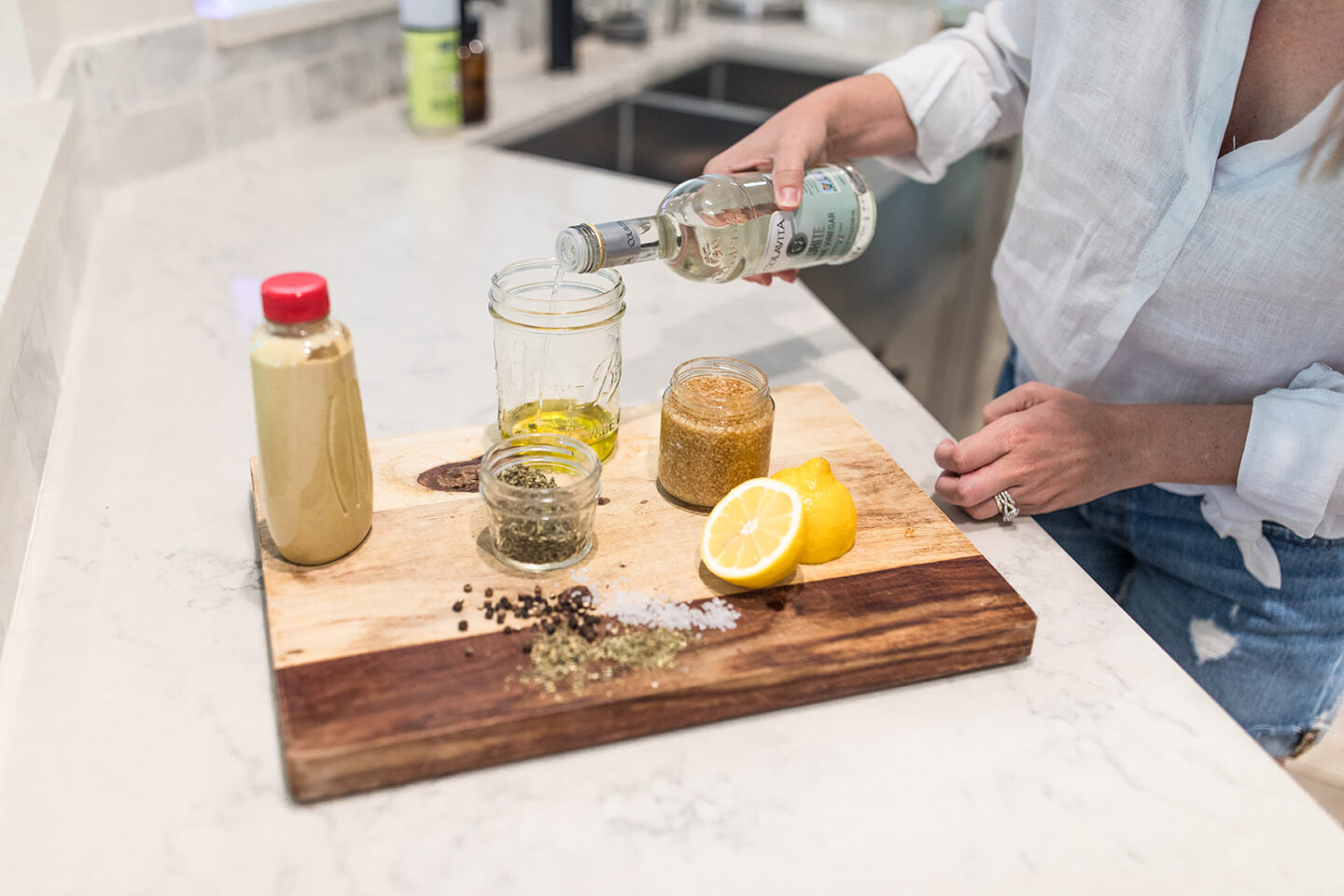 Easy Homemade Salad Dressing Recipe featured by top Atlanta lifestyle blogger, Moderately High Maintenance | Homemade Salad Dressing by popular Atlanta lifestyle blog, Moderately High Maintenance: image of a woman pouring vinegar into a mason jar.