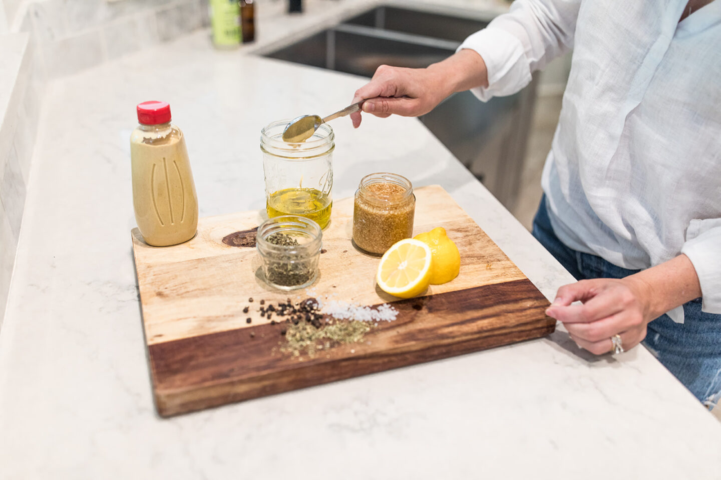 Easy Homemade Salad Dressing Recipe featured by top Atlanta lifestyle blogger, Moderately High Maintenance | Homemade Salad Dressing by popular Atlanta lifestyle blog, Moderately High Maintenance: image of woman putting mustard in a mason jar.