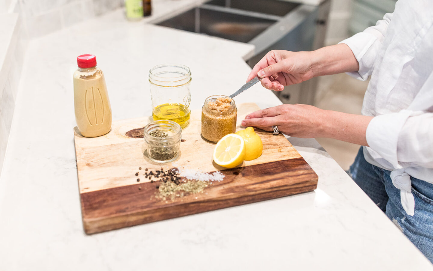 Easy Homemade Salad Dressing Recipe featured by top Atlanta lifestyle blogger, Moderately High Maintenance | Homemade Salad Dressing by popular Atlanta lifestyle blog, Moderately High Maintenance: image of a woman scooping some minced garlic out of a jar with a metal spoon.