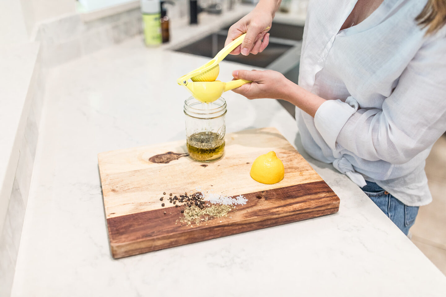 Easy Homemade Salad Dressing Recipe featured by top Atlanta lifestyle blogger, Moderately High Maintenance | Homemade Salad Dressing by popular Atlanta lifestyle blog, Moderately High Maintenance: image of a woman squeezing some lemon juice into a mason jar.
