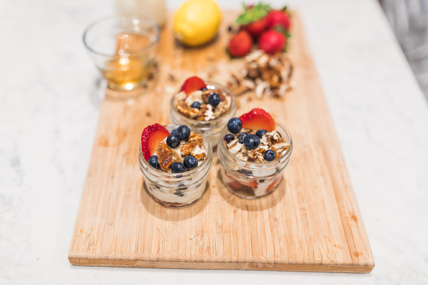 Vegan Berry Parfait Recipe featured by top Atlanta lifestyle blogger, Moderately High Maintenance | Vegan Parfait by popular Atlanta lifestyle blog, Moderately High Maintenance: image of yogurt parfaits with blueberries, strawberries, and chopped nuts in mason jars.
