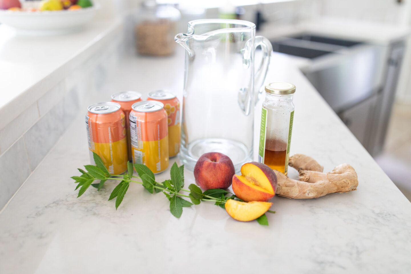 Easy Peach Mocktail Recipe featured by top Atlanta lifestyle blogger, Moderately High Maintenance | Peach Mocktail by popular Atlanta lifestyle blog, Moderately High Maintenance: image of a glass pitcher, peaches, gingers, and canned soda.