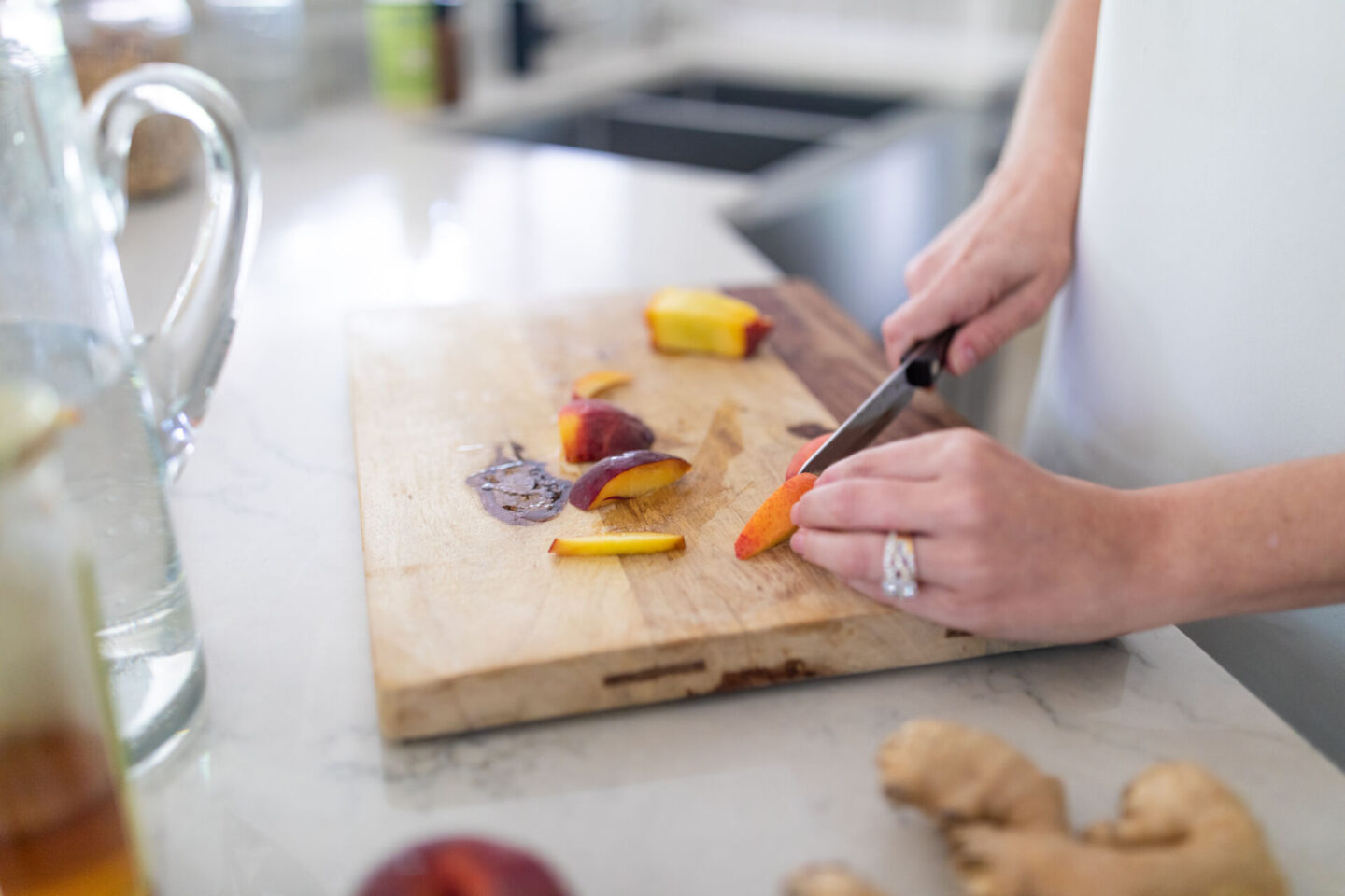 Easy Peach Mocktail Recipe featured by top Atlanta lifestyle blogger, Moderately High Maintenance | Peach Mocktail by popular Atlanta lifestyle blog, Moderately High Maintenance: image of a woman slicing some peaches on a wooden cutting board.