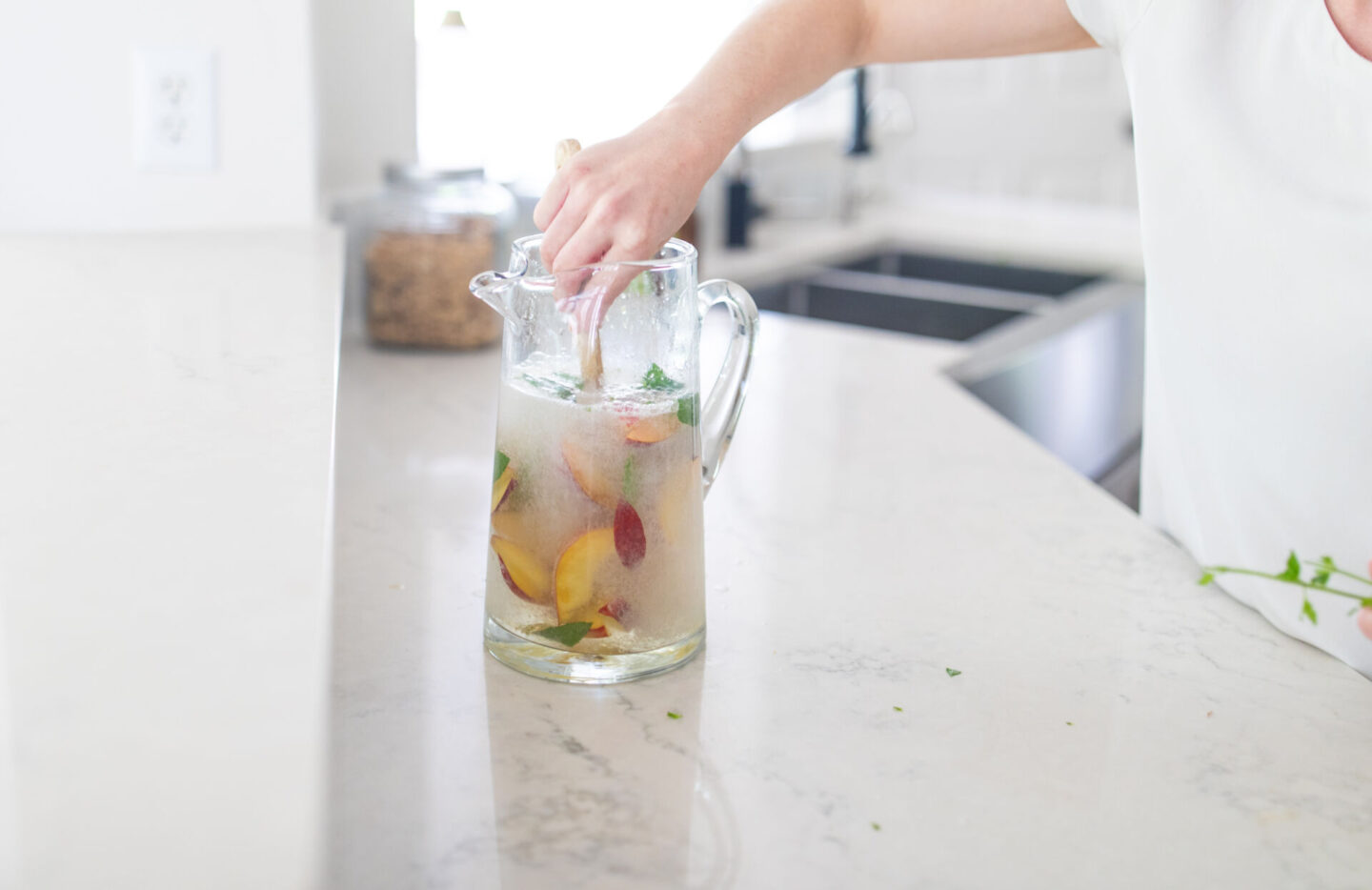 Easy Peach Mocktail Recipe featured by top Atlanta lifestyle blogger, Moderately High Maintenance | Peach Mocktail by popular Atlanta lifestyle blog, Moderately High Maintenance: image of a woman making a peach mocktail.