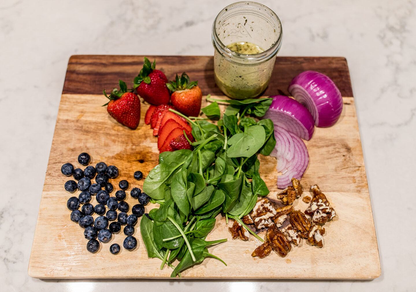 Easy Vegan Spinach and Berry Salad with pecans, a recipe featured by top Atlanta lifestyle blogger, Moderately High Maintenance   Berry Salad Recipe by popular Atlanta lifestyle blog, Moderately High Maintenance: image of strawberries, blueberries, spinach, red onions, salad dressing in a mason jar, and candied pecans on a wooden cutting board.