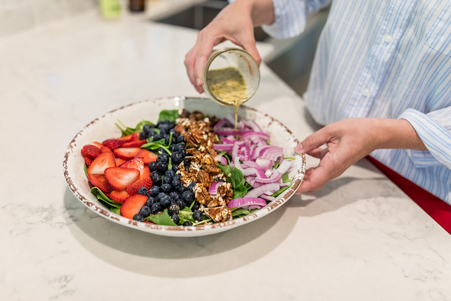Easy Vegan Spinach and Berry Salad with pecans, a recipe featured by top Atlanta lifestyle blogger, Moderately High Maintenance   Berry Salad Recipe by popular Atlanta lifestyle blog, Moderately High Maintenance: image of a woman making a spinach and berry salad.